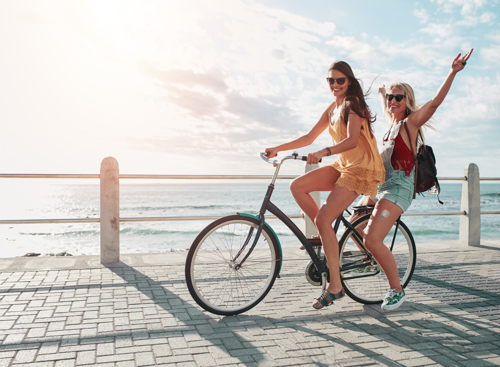 two happy young women riding a bike, one of which is wearing an omnipod insulin pump for type 1 diabetes