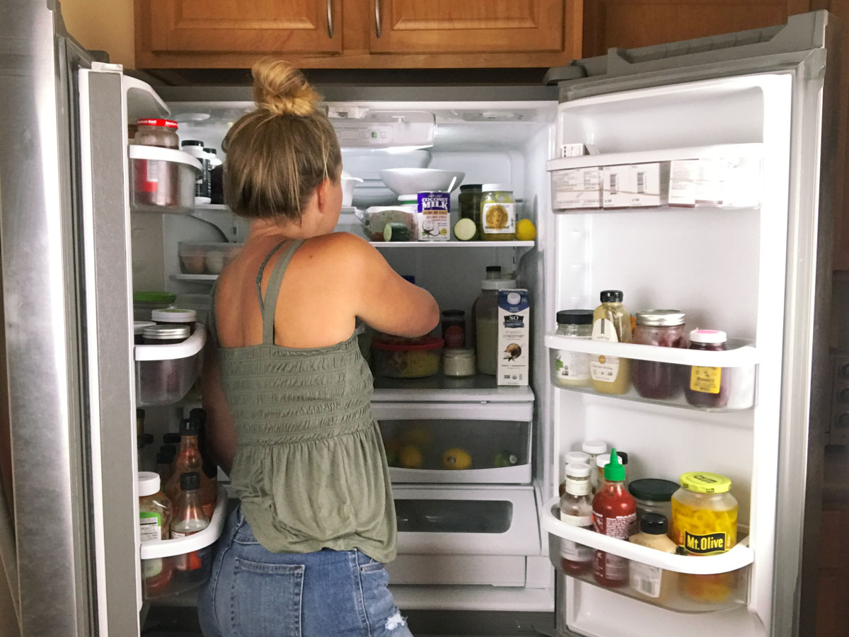 woman reaching into fridge for a snack