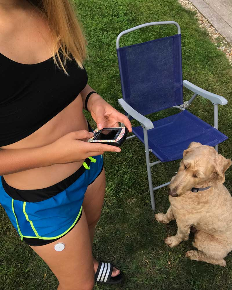 girl with type 1 diabetes using omnipod insulin pump PDM with godlendoodle in background
