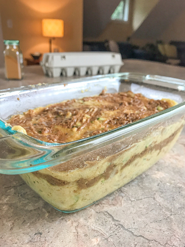 batter of cinnamon swirl zucchini bread in glass loaf pan so you can see layering